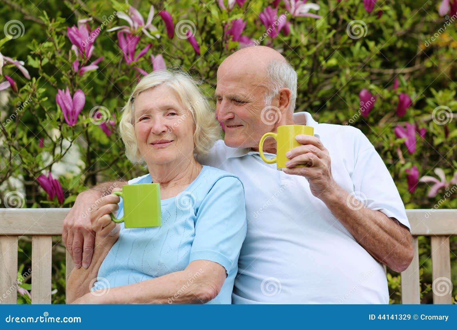 Chá bebendo dos pares superiores loving no jardim
