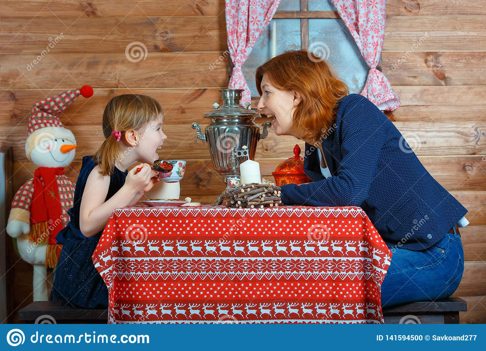 Chá da bebida da mamã e da filha de um samovar e de uma conversa