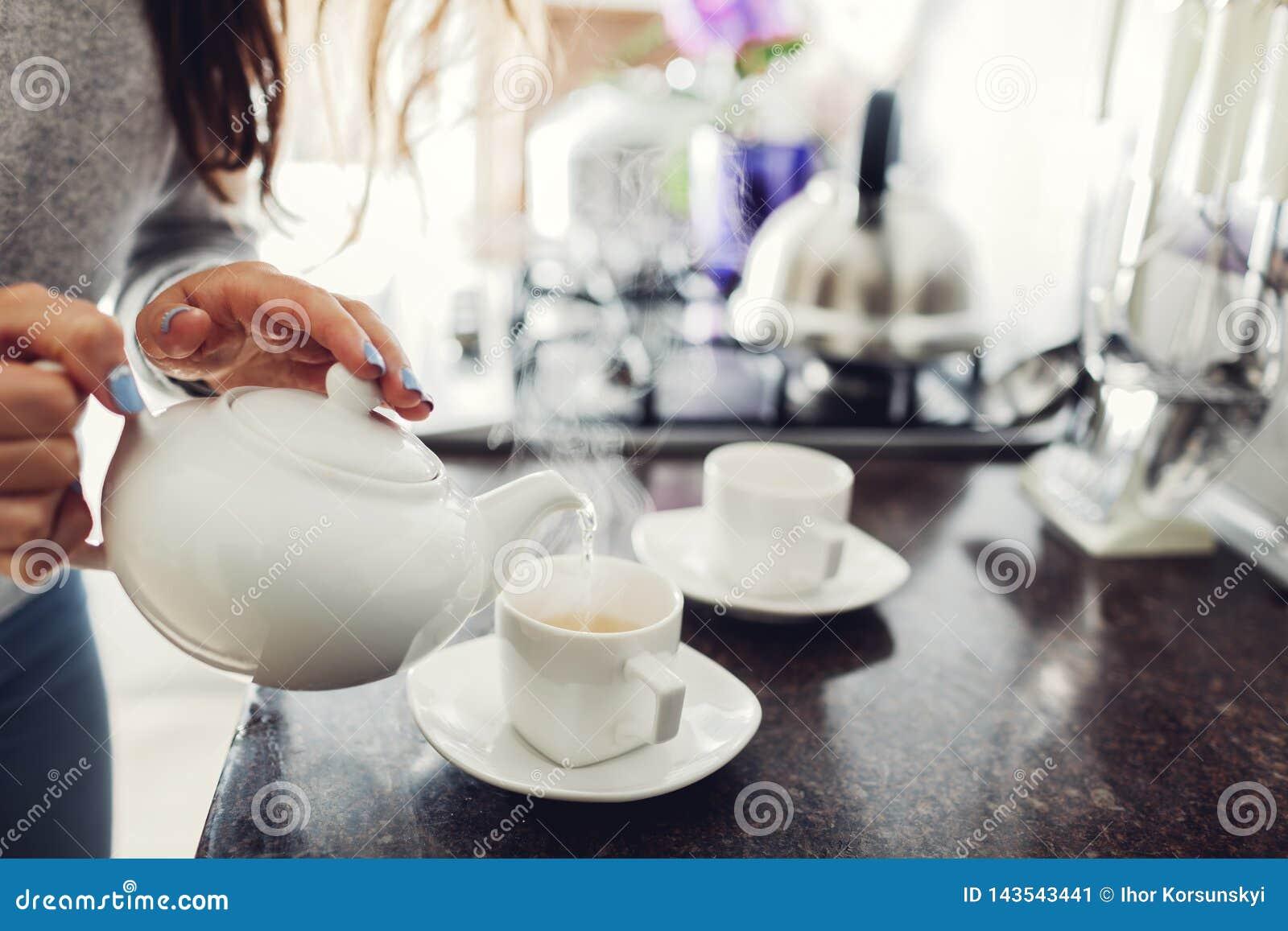 Chá de derramamento da mulher no copo cerâmico na tabela