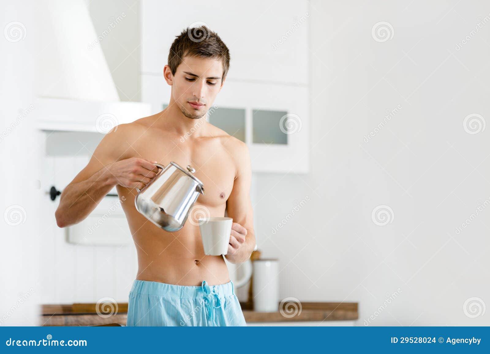 Chá de derramamento masculino semi-nua na cozinha