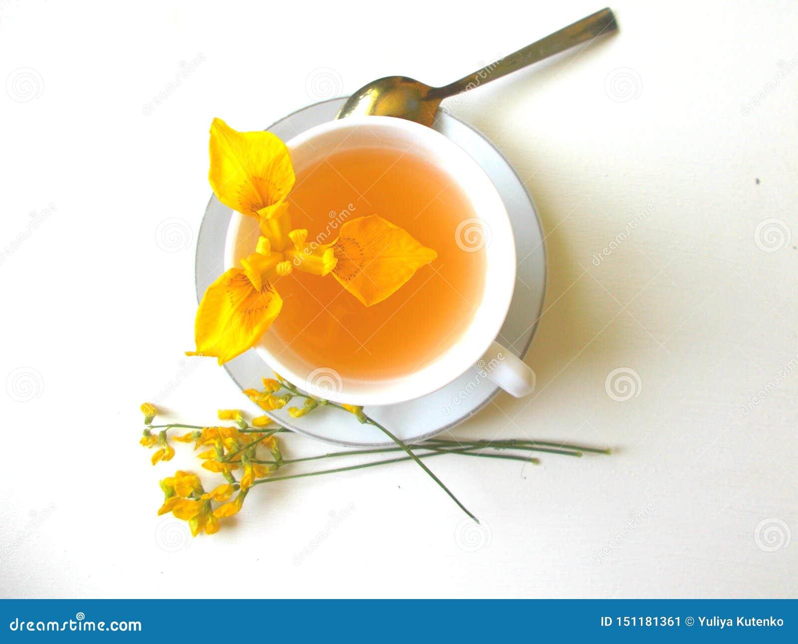 Chá em um copo branco com flores amarelas