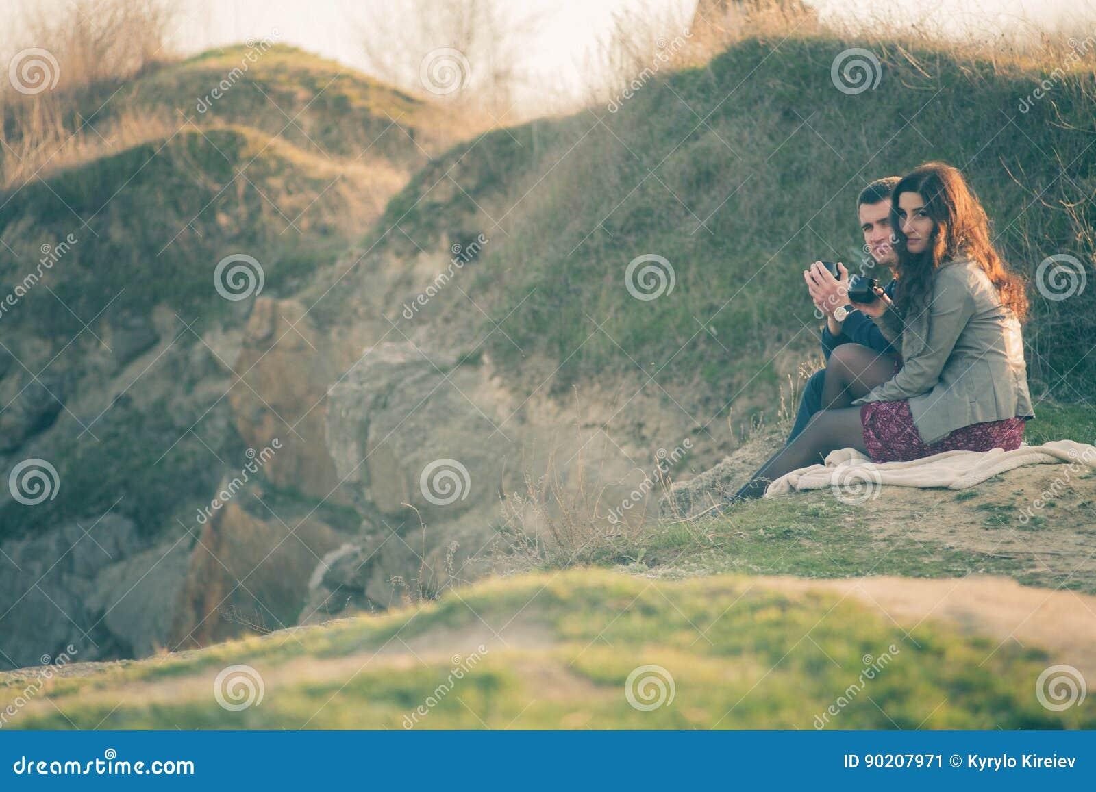 Chá exterior dos pares novos loving junto, bebendo feliz Um indivíduo com uma menina no lago no por do sol bebe o chá