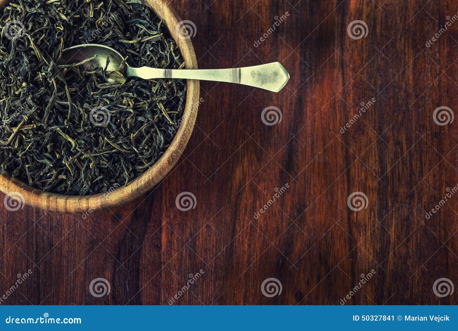 Chá seco na placa de madeira na tabela de madeira