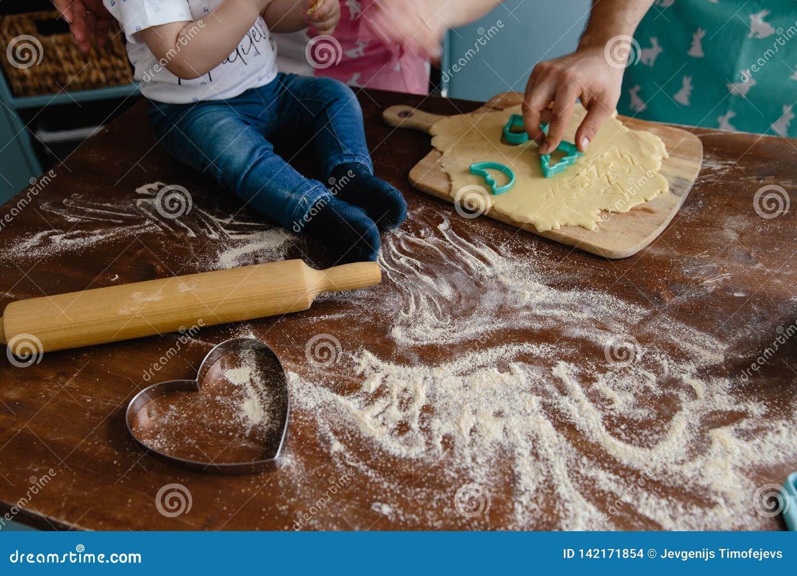 Chłopiec miesza mąkę w kuchni na stole robi niektóre bałaganić w cajgach