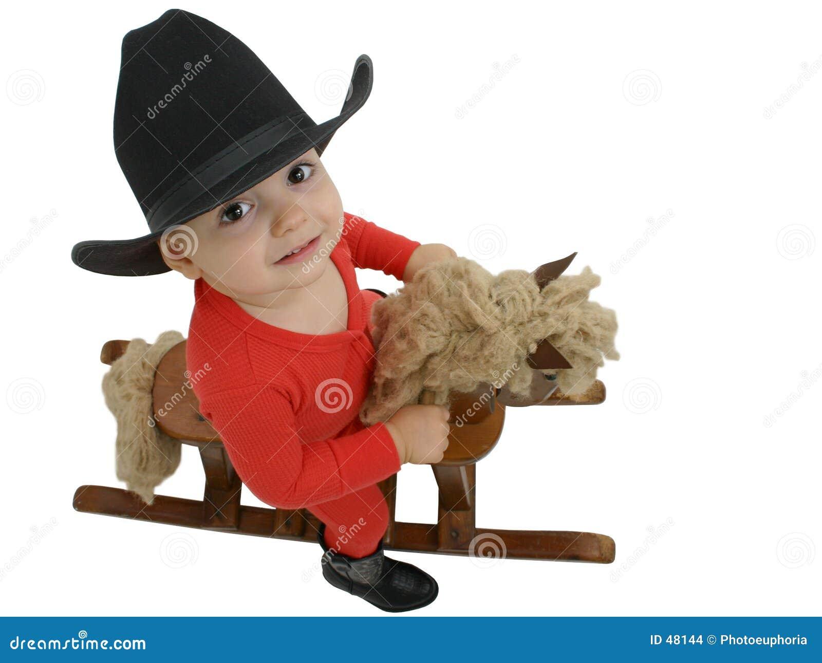 Chéri de cowboy avec le chapeau noir sur un cheval d oscillation