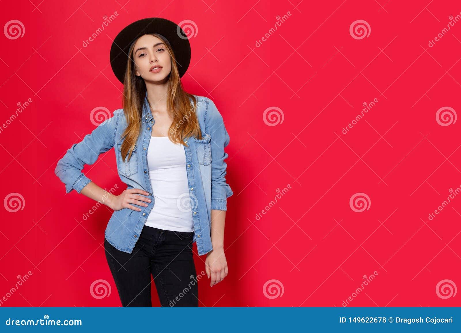Ch?odno dziewczyna w modnych str?j pozach z attitudine w studiu na czerwonym jaskrawym tle miejsce tekst