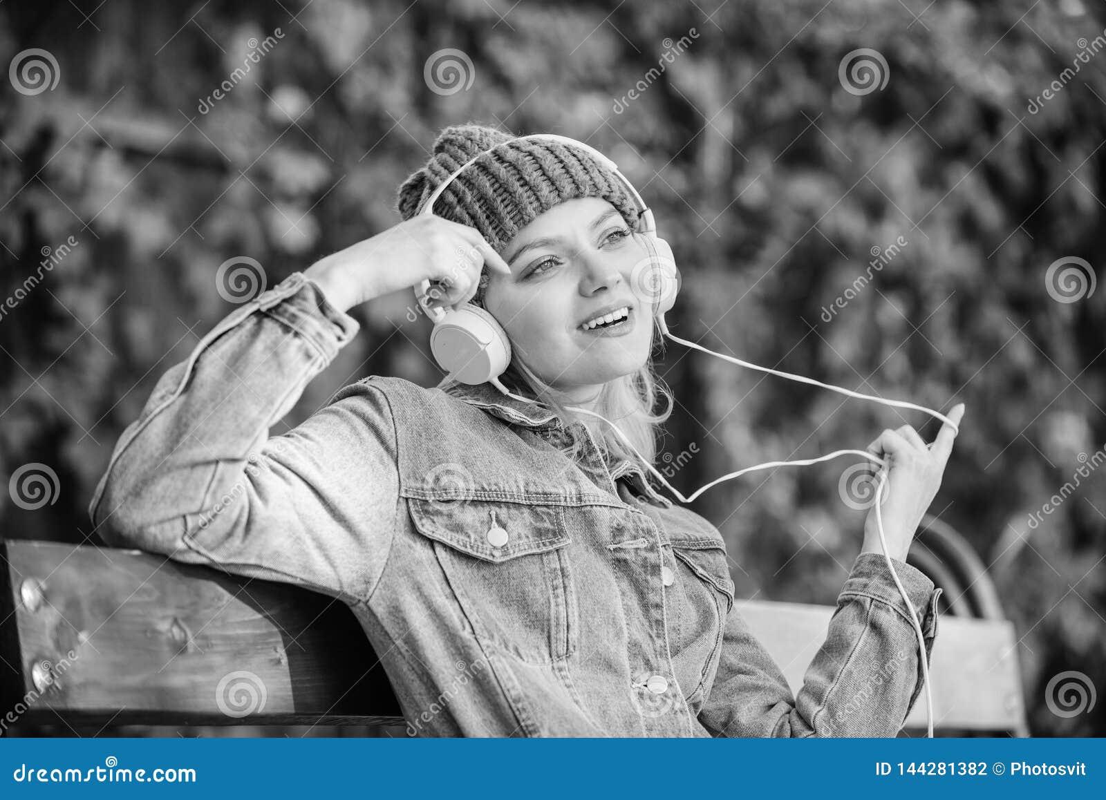 Chłodno ostra dziewczyna cieszy się muzykę w hełmofonach plenerowych Dziewczyna słucha muzykę w parku Melodia dźwięk i mp3 Fan mu