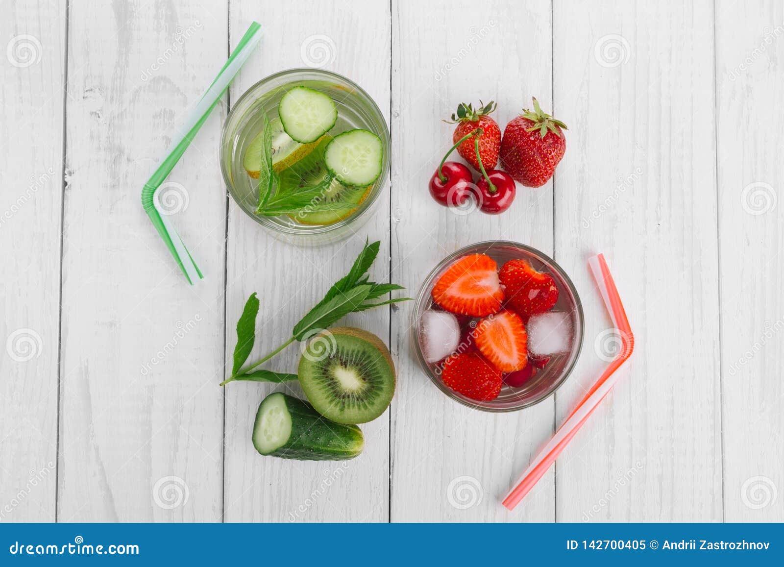 Chłodno woda w szkle, świeżym zielonym kiwi, mennica, ogórek, truskawki i wiśnie, Świeże domowej roboty witaminy