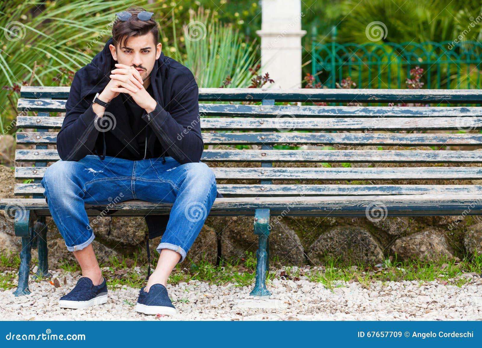 Chłopaka czekanie Przystojny młodego człowieka modela obsiadanie na ławce