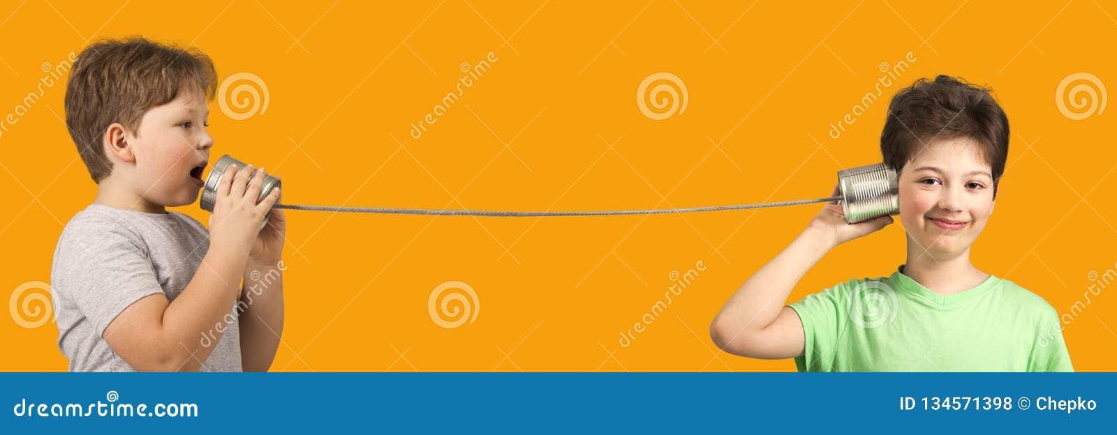 Chłopiec Bawić się z Blaszanej puszki telefonem Odizolowywający na Pomarańczowym tle