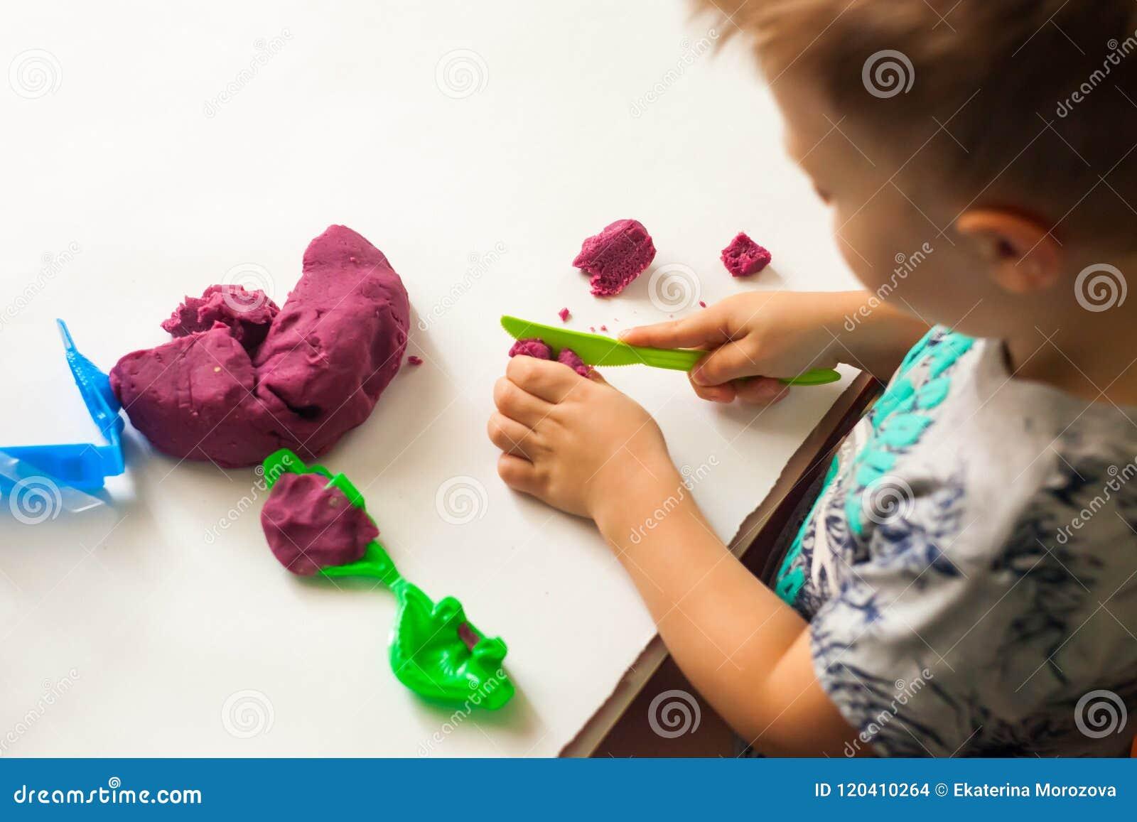Chłopiec bawić się z glinianym ciasta, edukaci i daycare pojęciem,