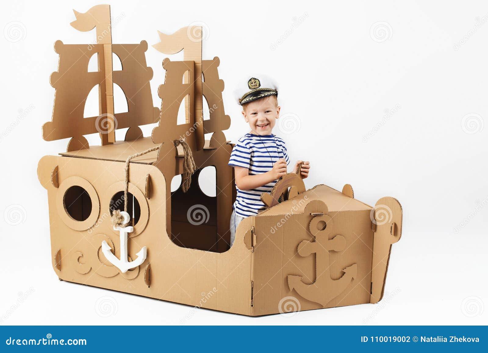 Chłopiec bawić się z kartonowym statkiem na białym tle Happ