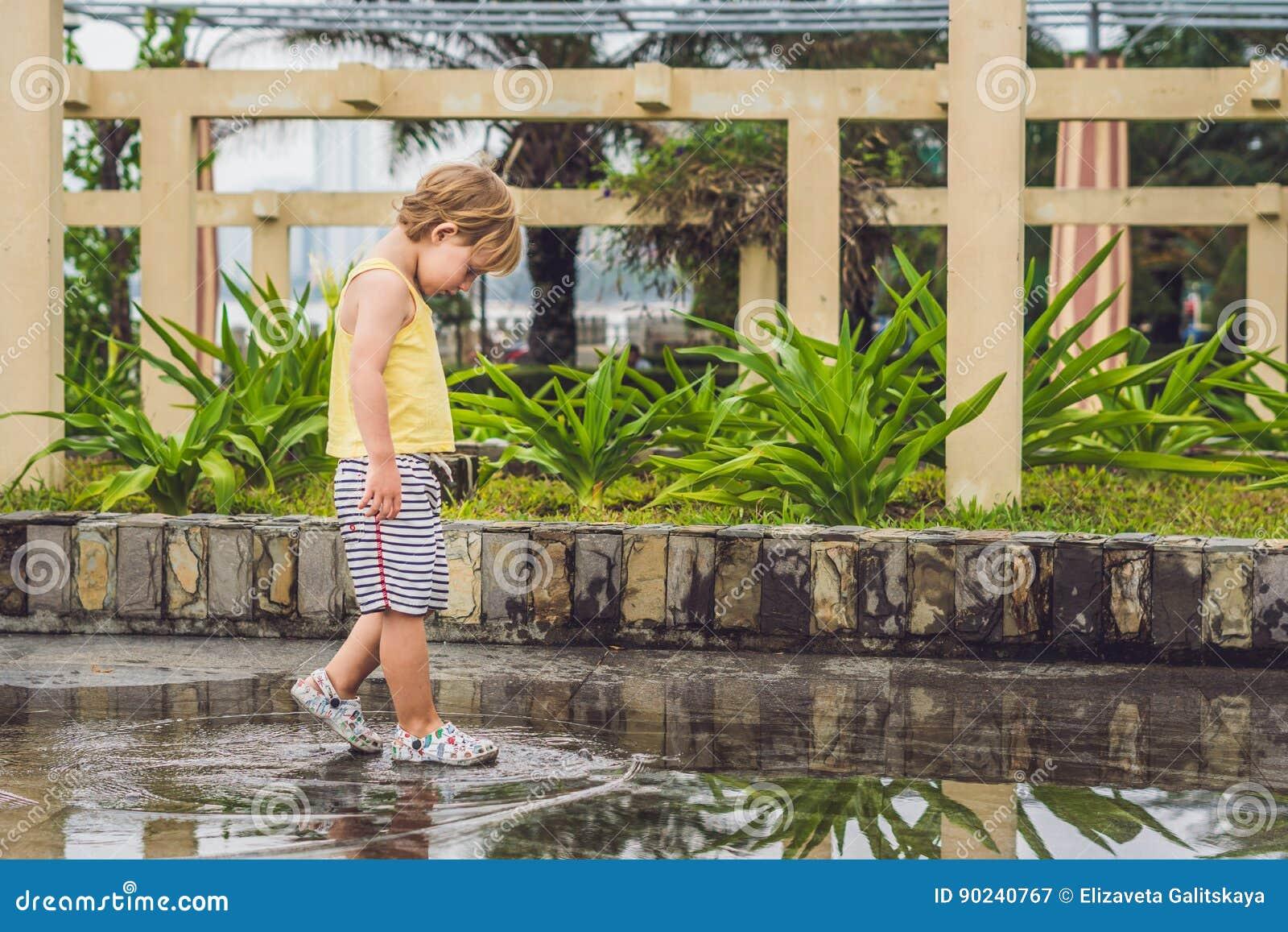 Chłopiec biega przez kałuży Lato plenerowy