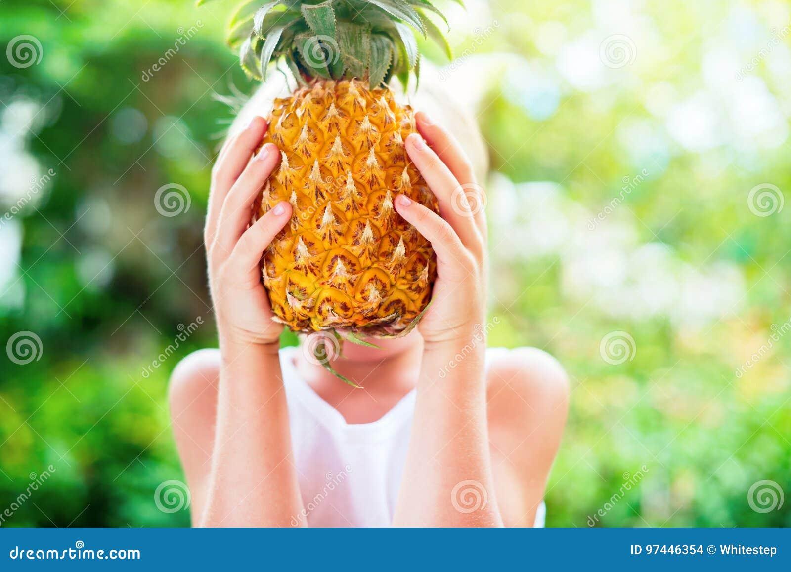 Chłopiec chwyta ananas Wręcza lata tło