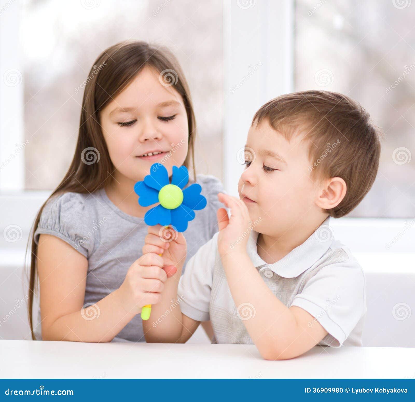 Chłopiec daje dziewczyna kwiatu