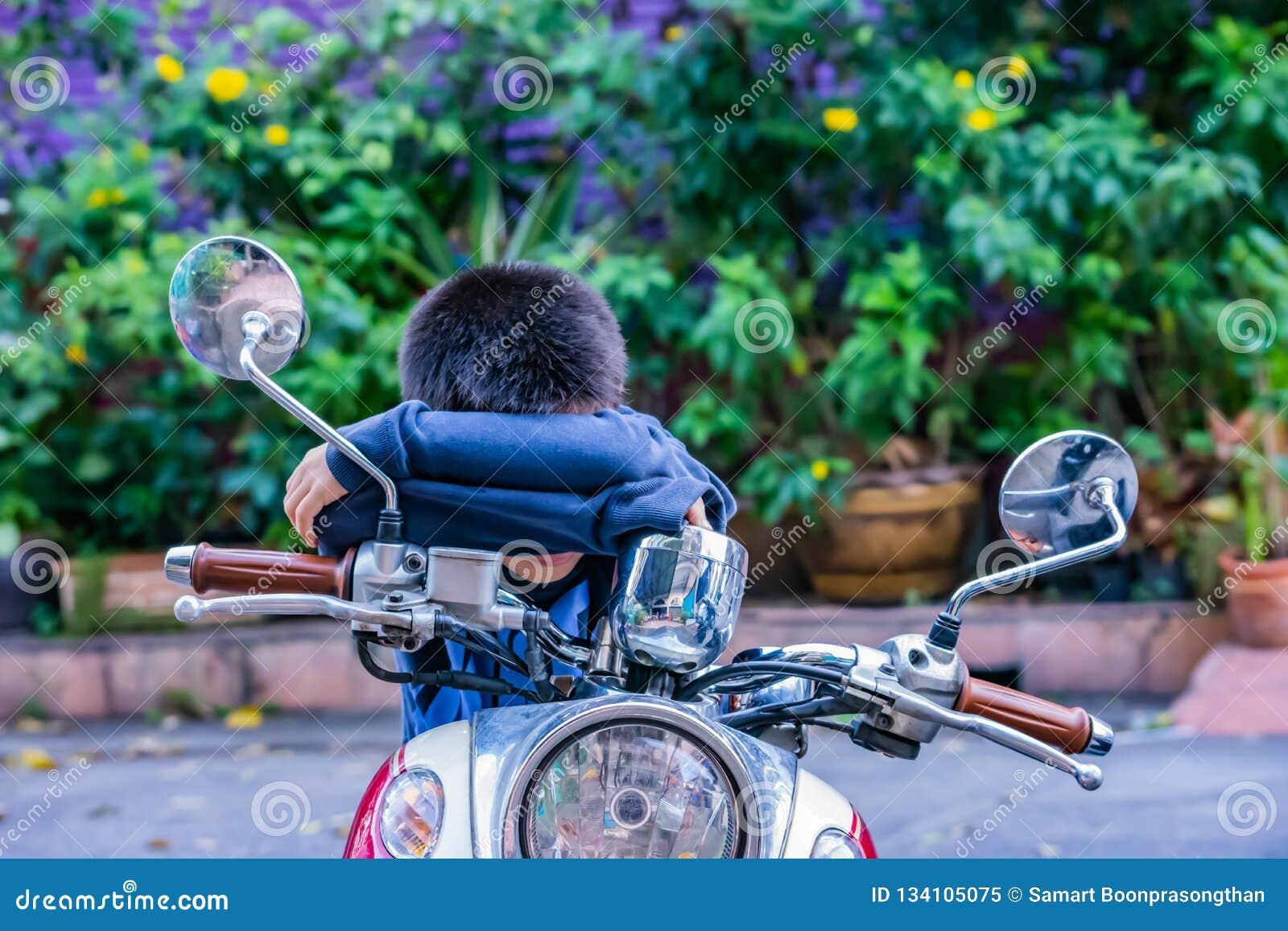 Chłopiec dosypianie na motocyklu i obsiadanie