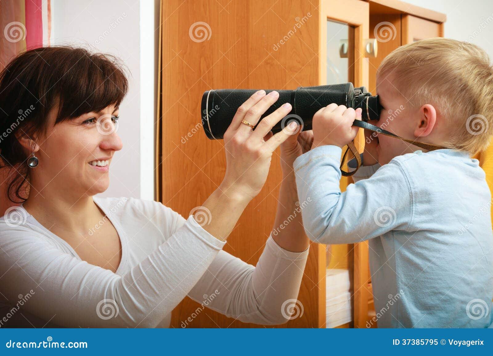 Chłopiec dziecka dzieciaka syn z kamerą bierze fotografii jego matka. W domu.