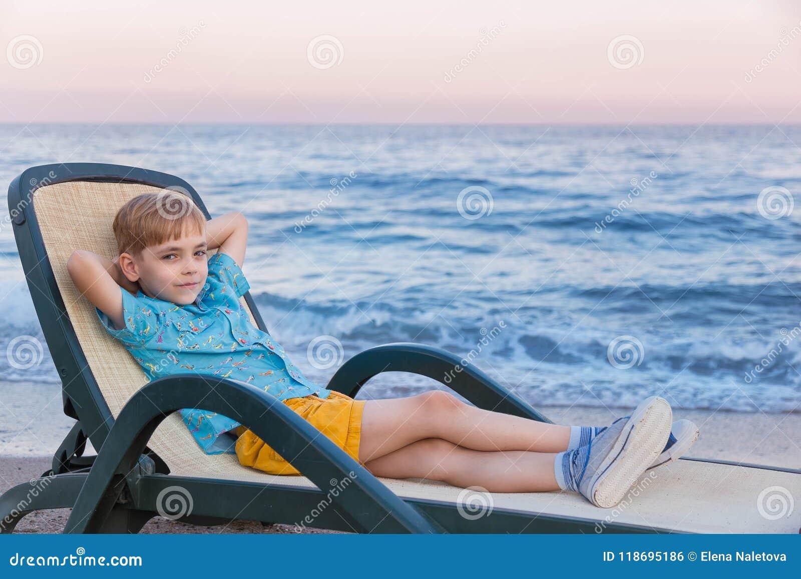 Chłopiec Europejski pojawienie w błękitnej pasiastej koszulce żółci skróty i polo odpoczynek w bryczka holu przy kipiel paskiem