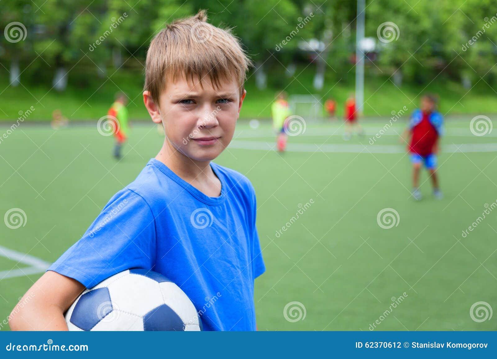 Chłopiec futbolista z piłką w stadium