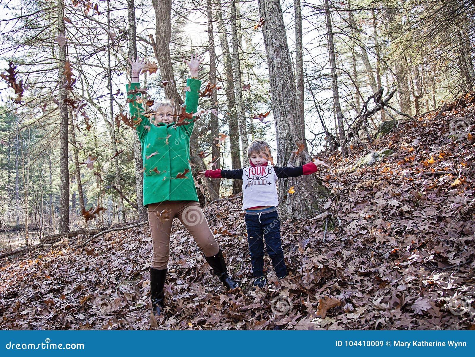 Chłopiec i babcia bawić się w liściach
