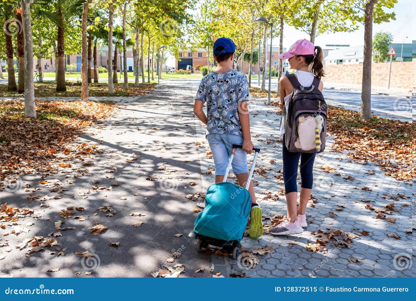 Chłopiec i dziewczyna opowiada iść szkoła z ich plecakami