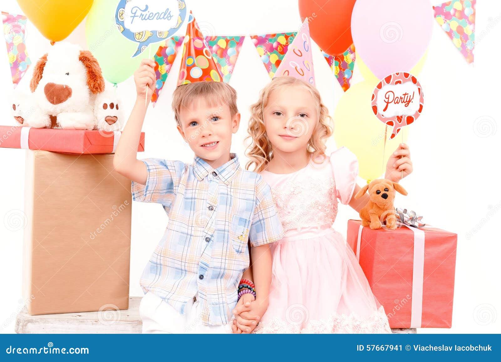 Chłopiec i dziewczyna pozuje podczas przyjęcia urodzinowego