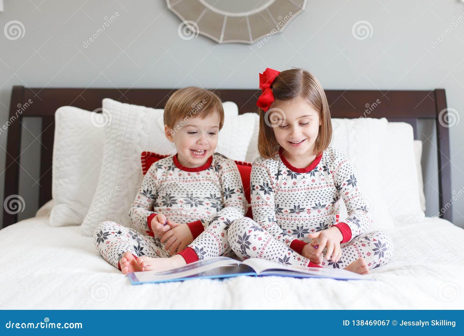Chłopiec i dziewczyny czytanie na łóżku z Bożenarodzeniowymi piżamami