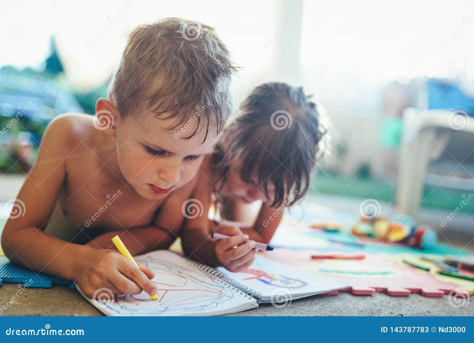 Chłopiec i dziewczyny rysunek z kredkami