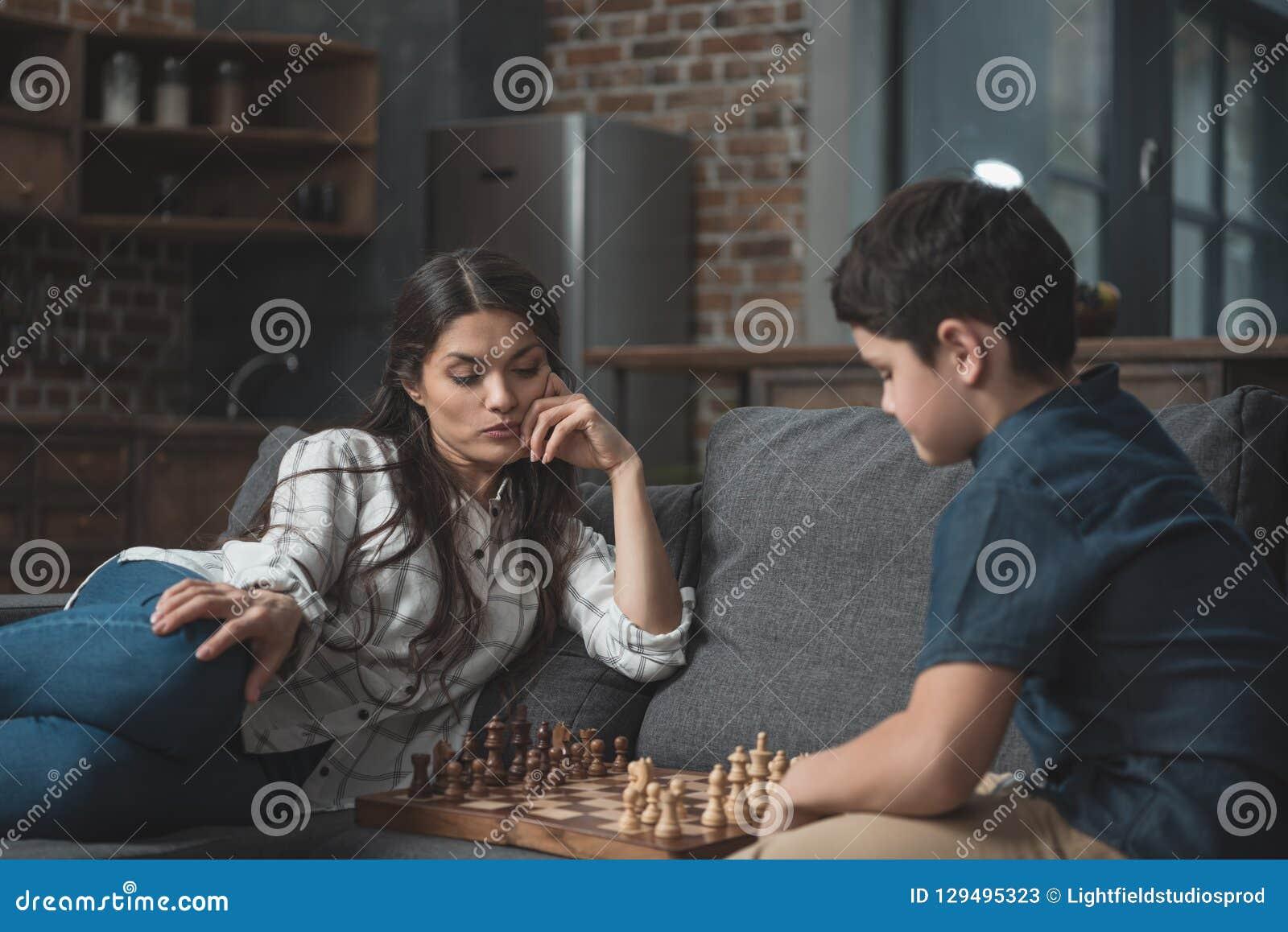 Chłopiec i jego młoda matka bawić się szachy na leżance