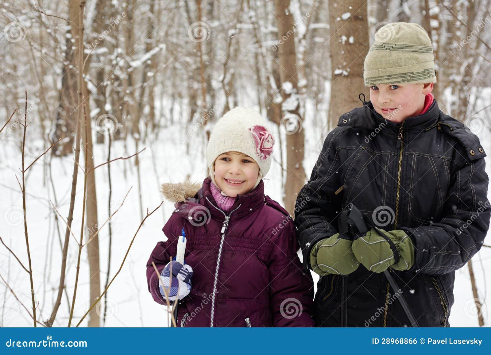 Chłopiec i jego siostrzany stojak w zima parku z narciarskimi słupami