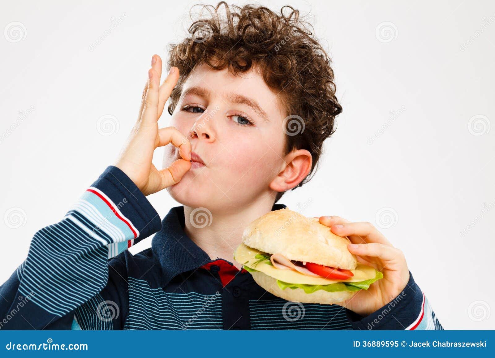 Chłopiec je dużą kanapkę