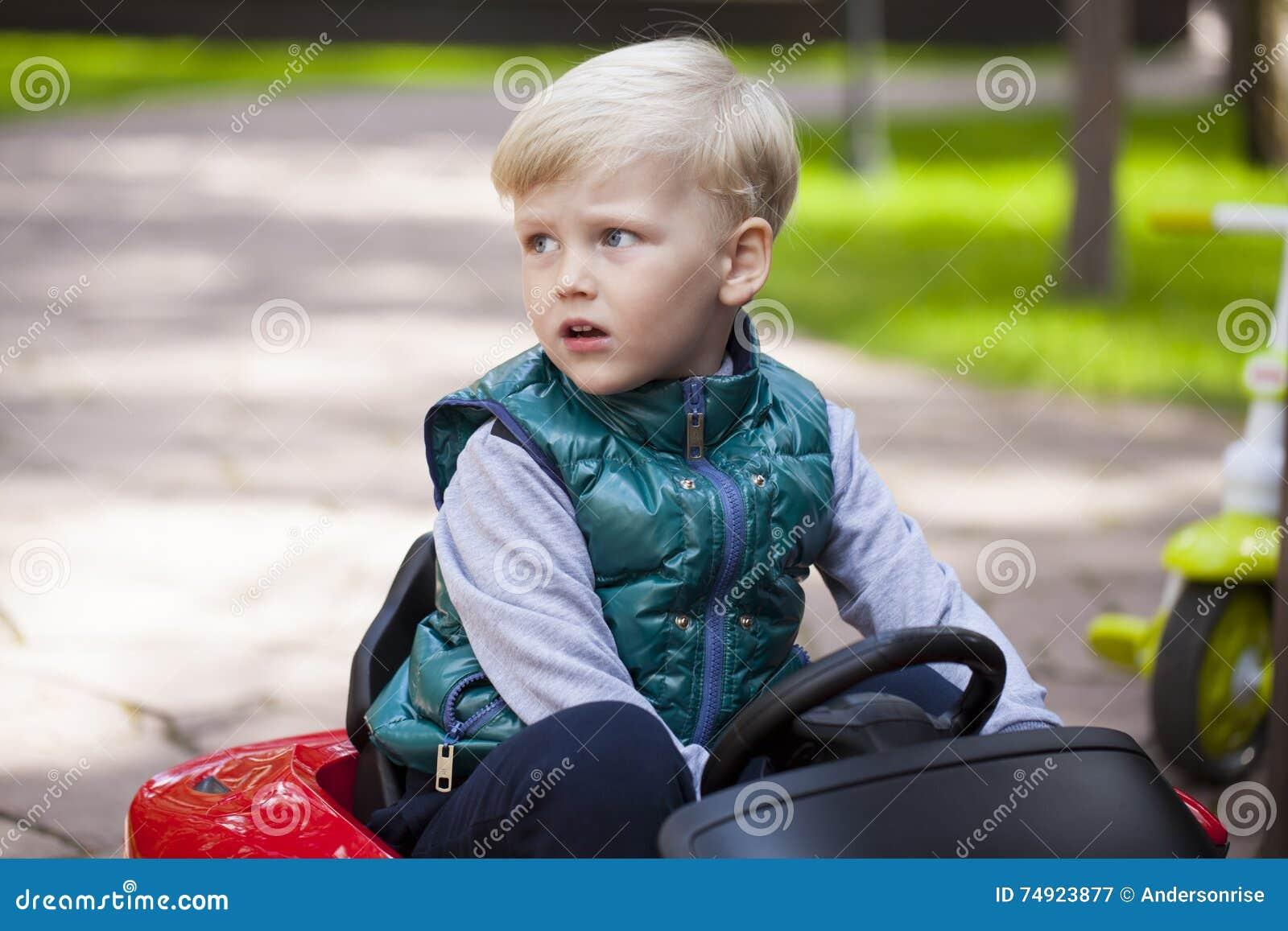 Chłopiec jedzie dużego zabawkarskiego samochód, wiosna outdoors