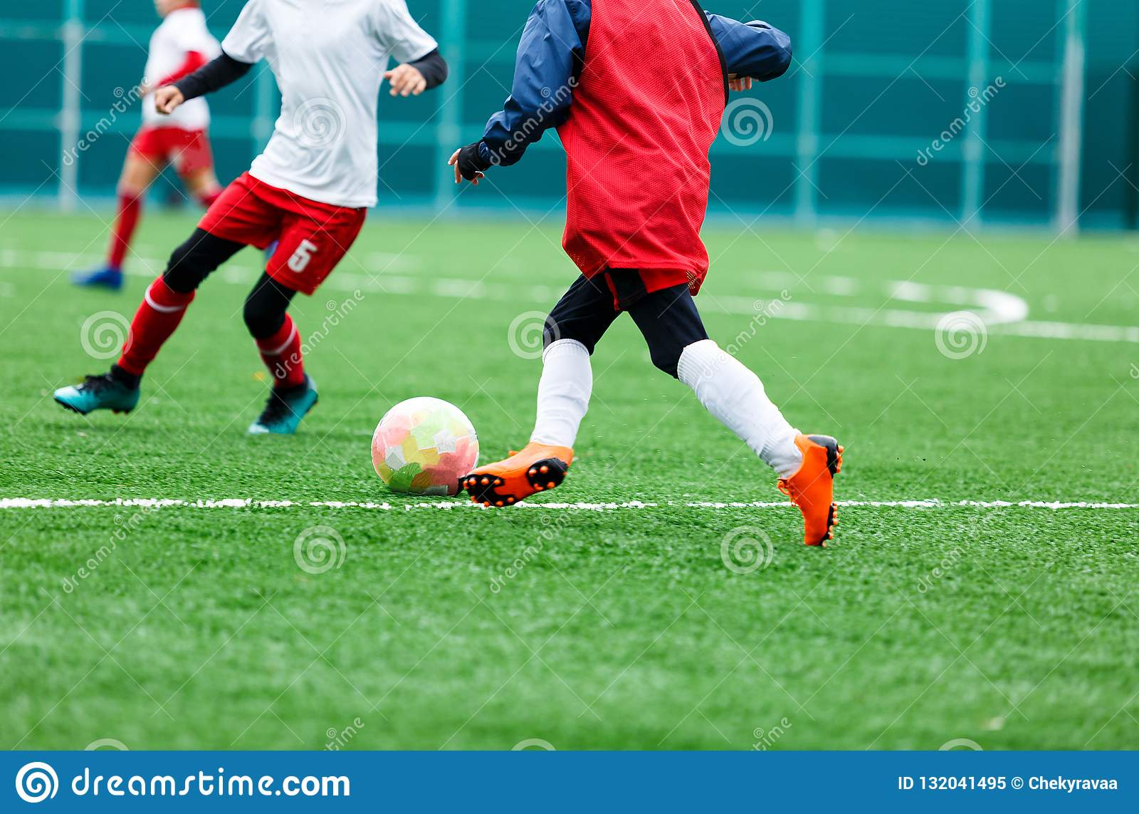 Chłopiec kopie piłki nożnej piłkę Chłopiec biega po piłki na zielonej trawie futbolista w białej i czerwonej koszula chłopiec dry