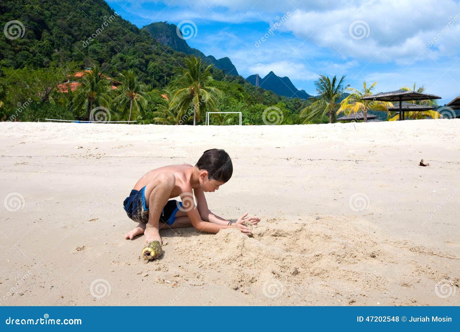 Chłopiec ma zabawę outdoors bawić się plażą w tropikalnej wyspie w piasku