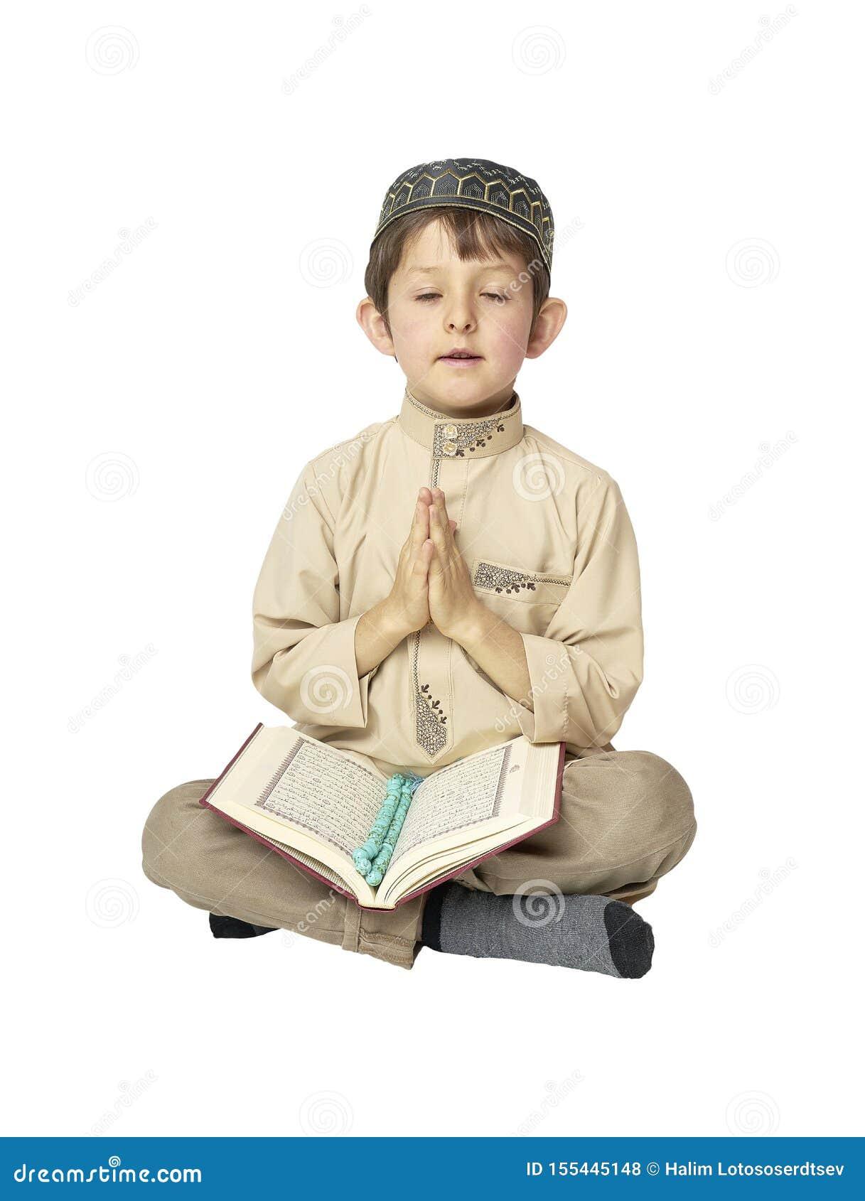 Chłopiec modlenie Koran z różanów koralikami na białym tle i mienie