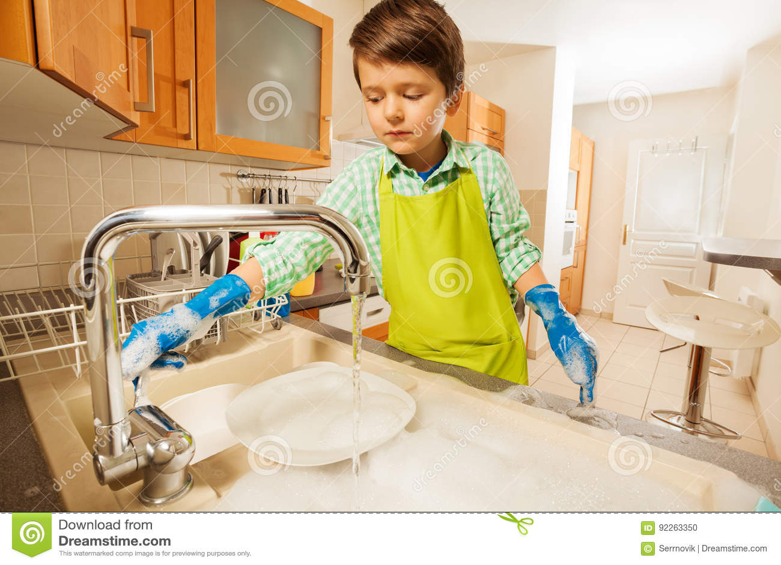 Chłopiec obraca dalej klepnięcie i opłukuje naczynia w zlew