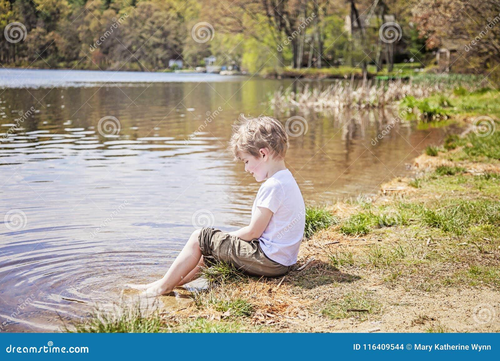 Chłopiec obsiadanie na brzeg jezioro