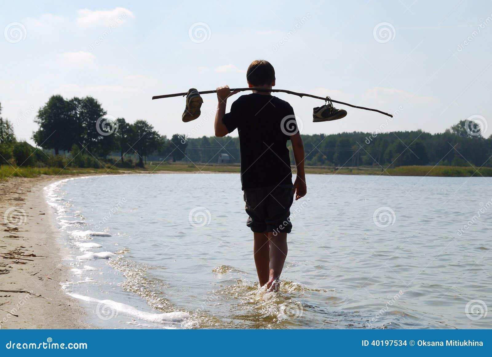 Chłopiec odprowadzenie na wodzie w plecy świetle