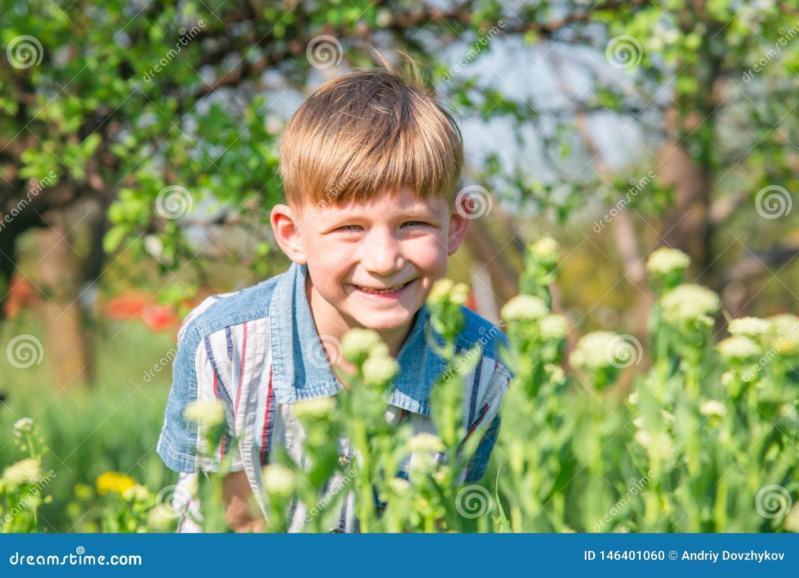 Chłopiec ono uśmiecha się i śmia się pod wiosny słońcem na tle krzaki i drzewa