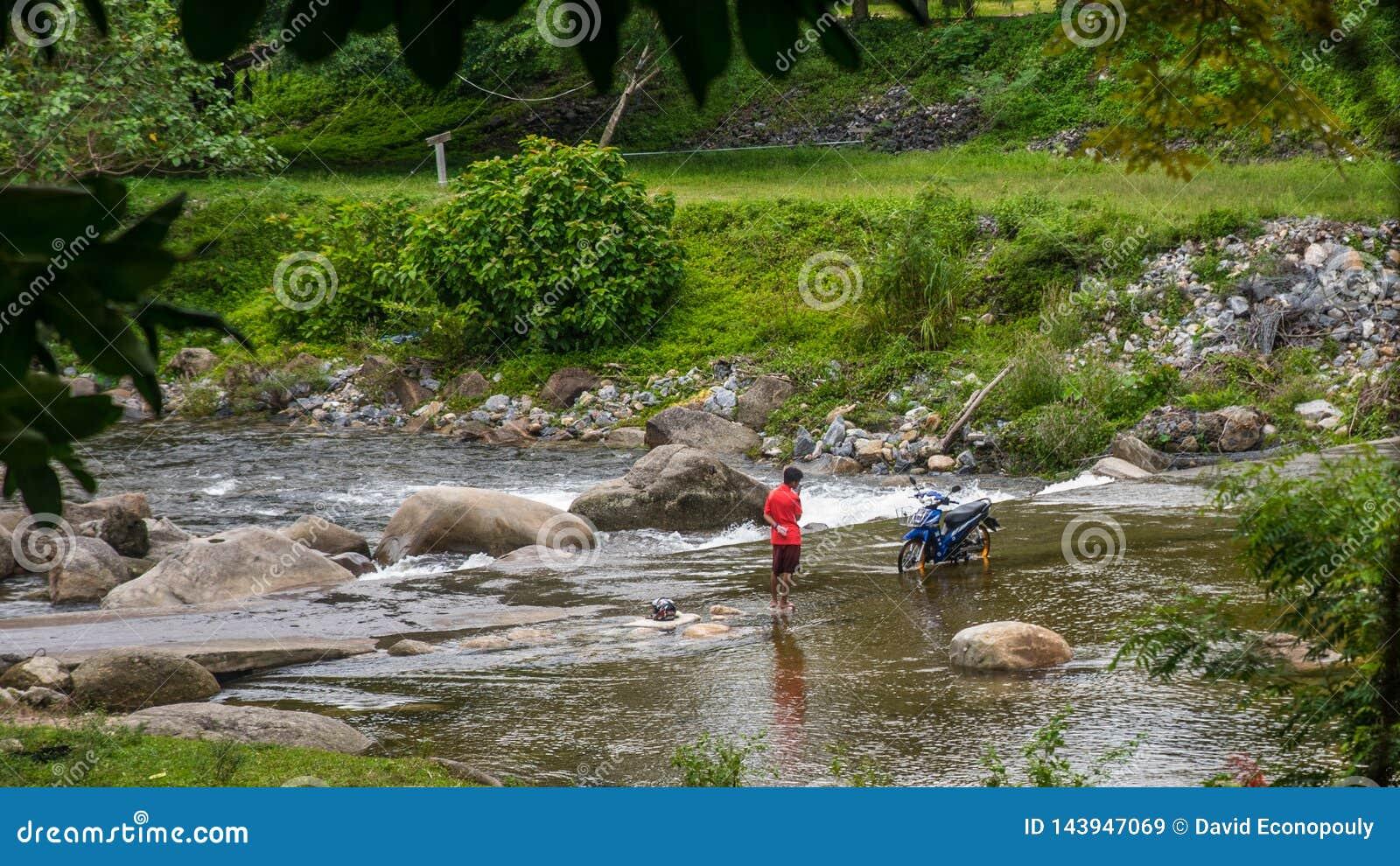Chłopiec płuczkowy motocykl w rzece