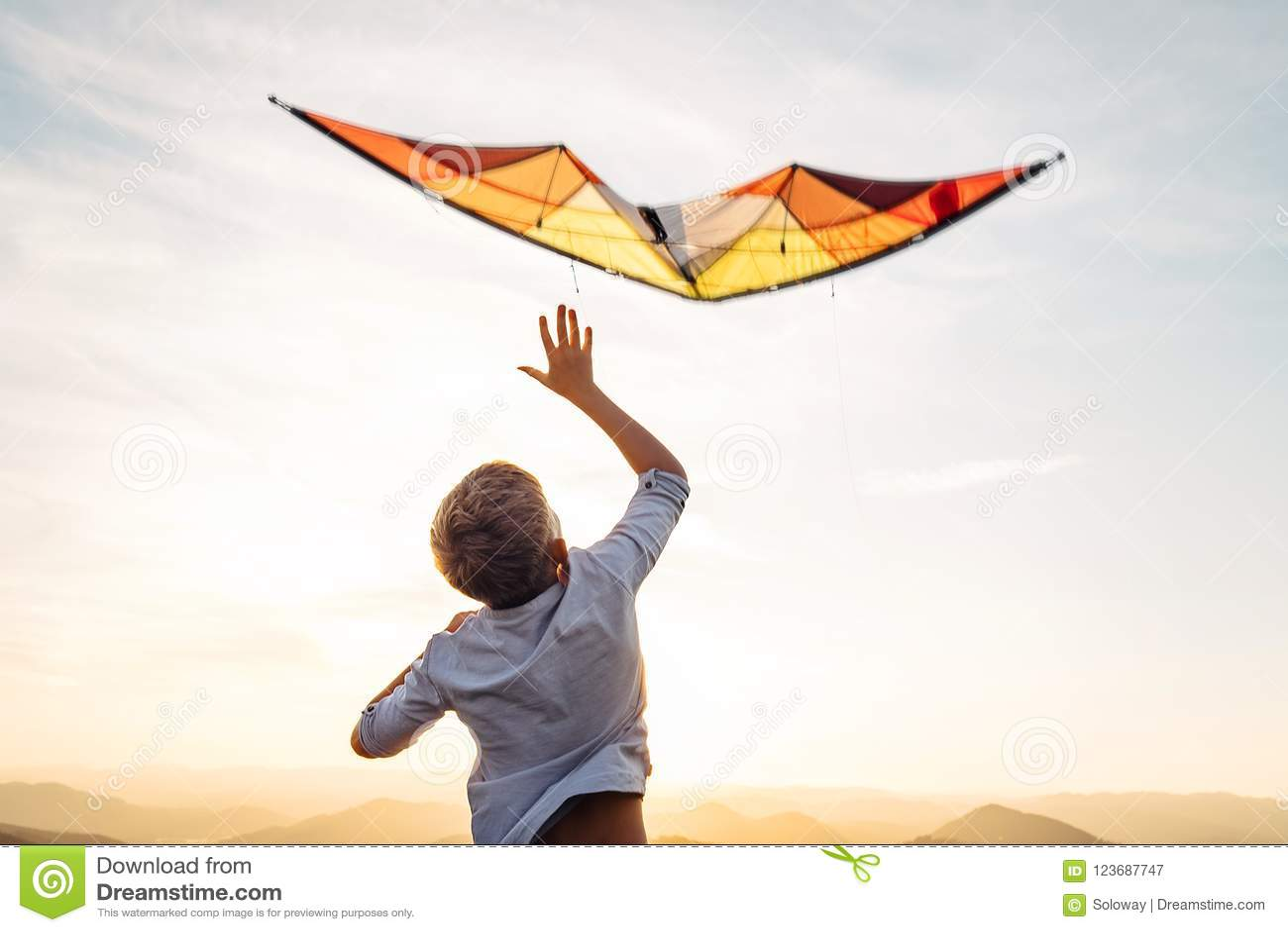 Chłopiec początek latać jaskrawą pomarańczową kanię w niebie