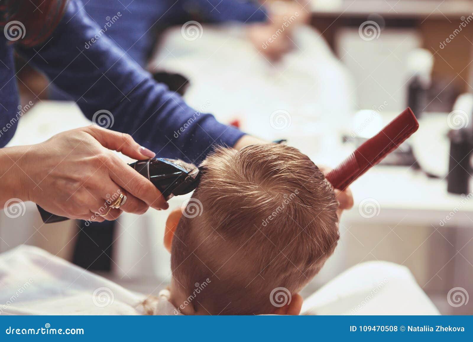 Chłopiec przy fryzjerem Dziecko okalecza ostrzyżenia hairball
