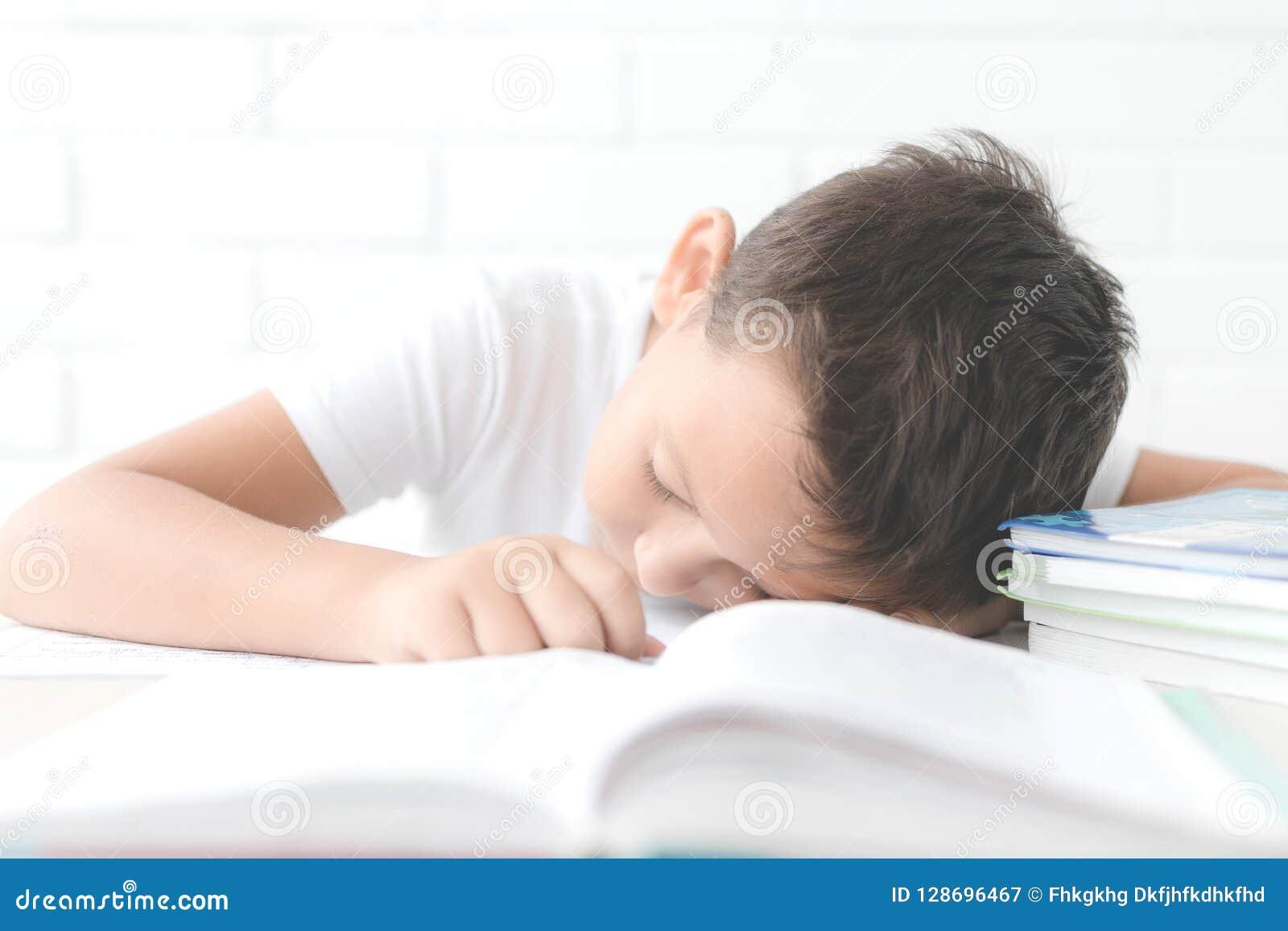 Chłopiec robi jego pracie domowej przy jego biurkiem w domu
