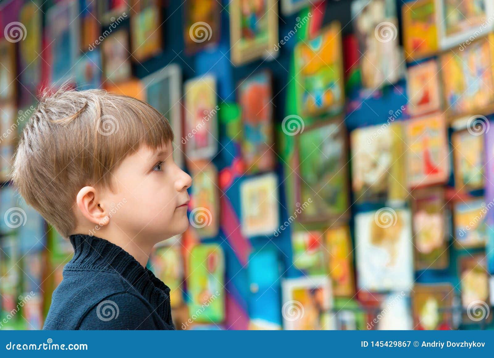 Chłopiec spojrzenia przy obrazami przy wystawą malarska sztuka i twórczość