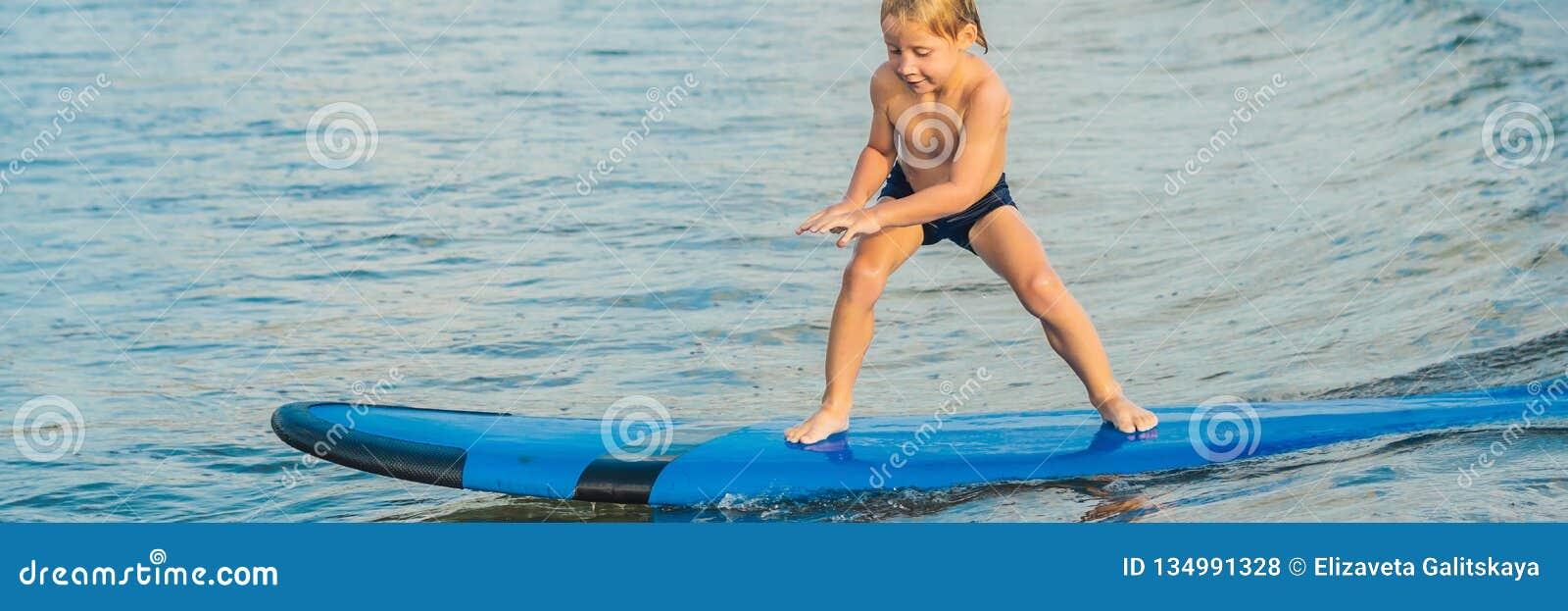 Chłopiec surfing na tropikalnej plaży Dziecko na kipieli desce na ocean fala Aktywni wodni sporty dla dzieciaków Dzieciaka dopłyn