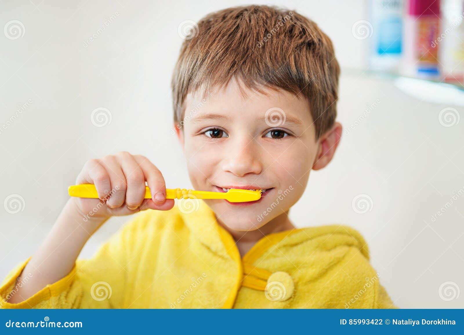 Chłopiec szczotkuje jego zęby w wannie, ono uśmiecha się, jasnopopielaty tło