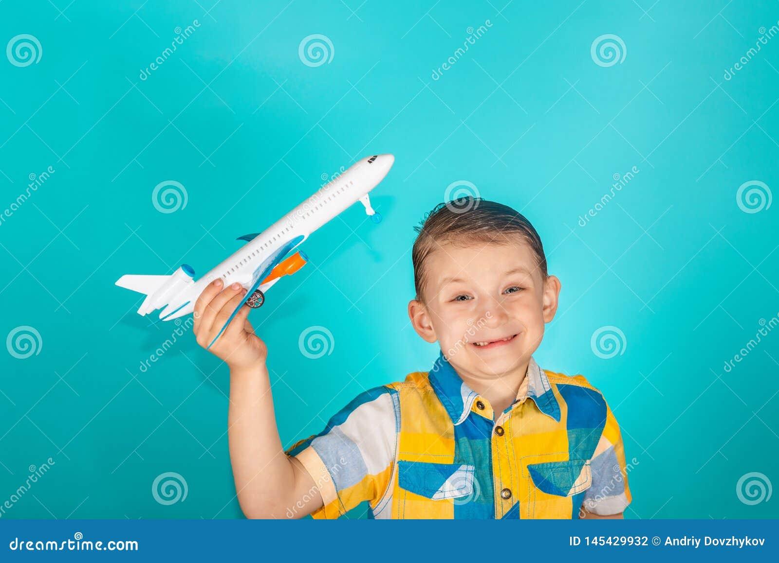 Chłopiec trzyma zabawkarskiego samolot w jego ręce i ono uśmiecha się w jaskrawej kolor koszula, fotografia w studiu na błękitnym