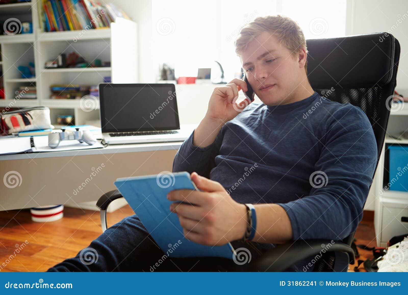 Chłopiec Używa Cyfrowego telefon komórkowego I pastylkę W sypialni