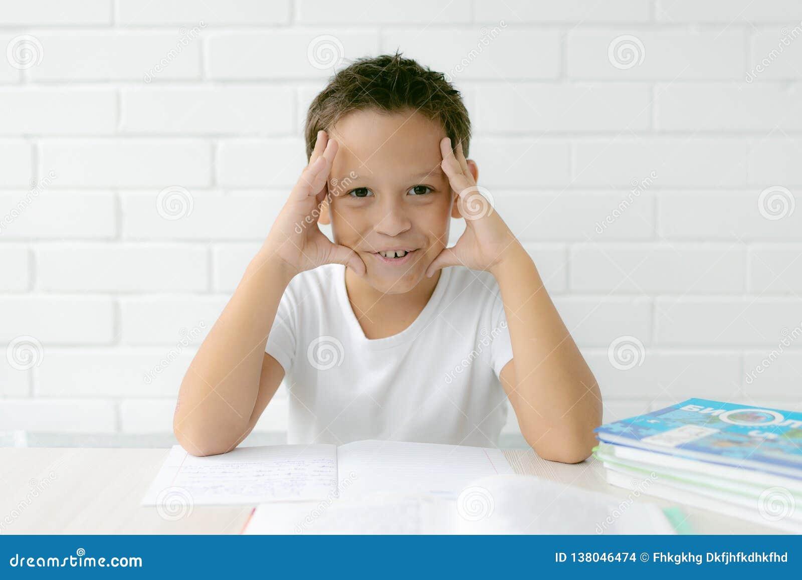 Chłopiec uczeń pisze w notatniku i czytelniczych książkach uczy lekcje