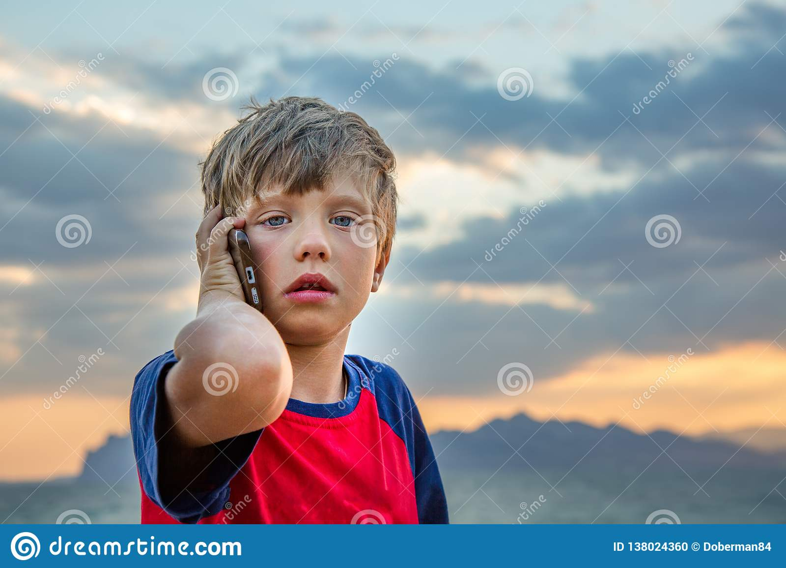 Chłopiec w czerwonej koszulce siedzi outdoors i opowiada na jego telefonie komórkowym, patrzeje spęczenie lub straszył Nastolatek
